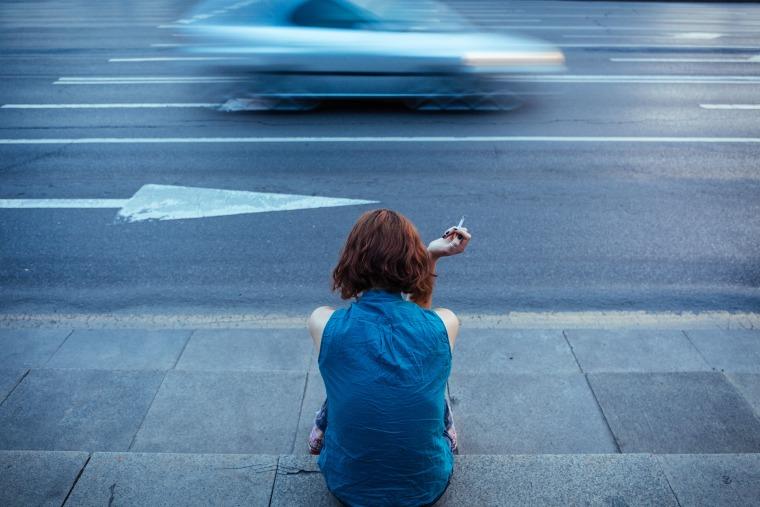 Teenager smoking on a sidewalk