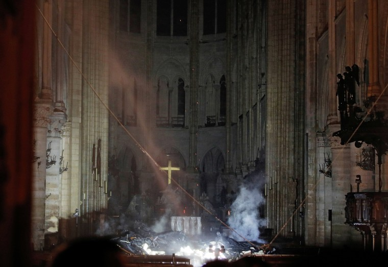 Image: Smoke rises around the altar in front of the cross inside the Notre Dame Cathedral as a fire continues to burn in Paris