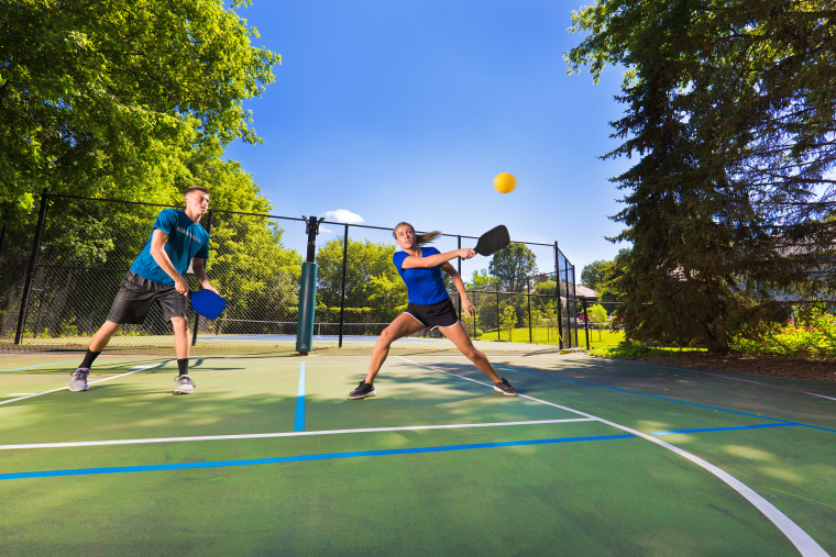 Image: Young Man and Woman Playing Pickleball in Court