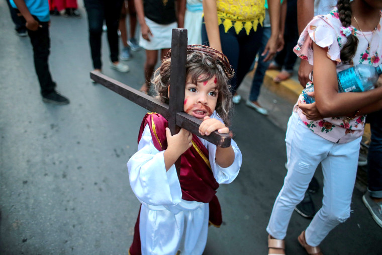 """Image: A child dressed as Jesus Christ carries a wooden cross during the """"Jesus del gran poder"""" procession in the colonial city of Granada"""