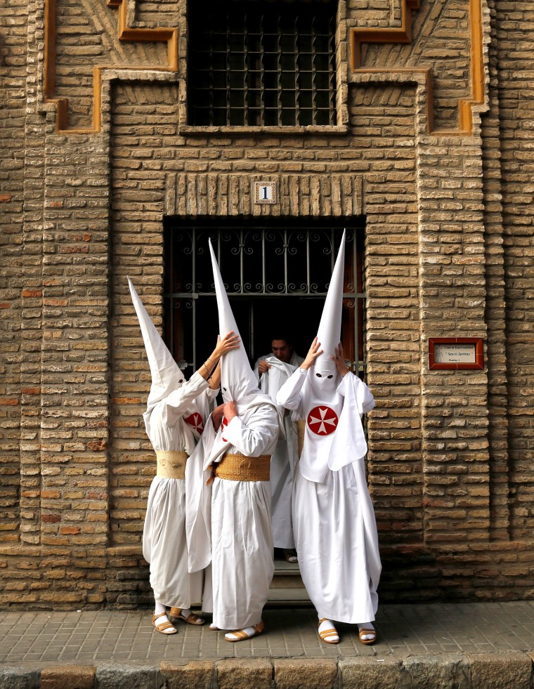 Image: Penitents of La Amargura brotherhood make their way to a church during Holy Week in the Andalusian capital of Seville