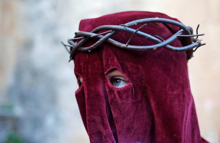 Image: A woman, penitent of Los Gitanos brotherhood, leaves a church as she takes part in a procession during Holy Week in Ronda