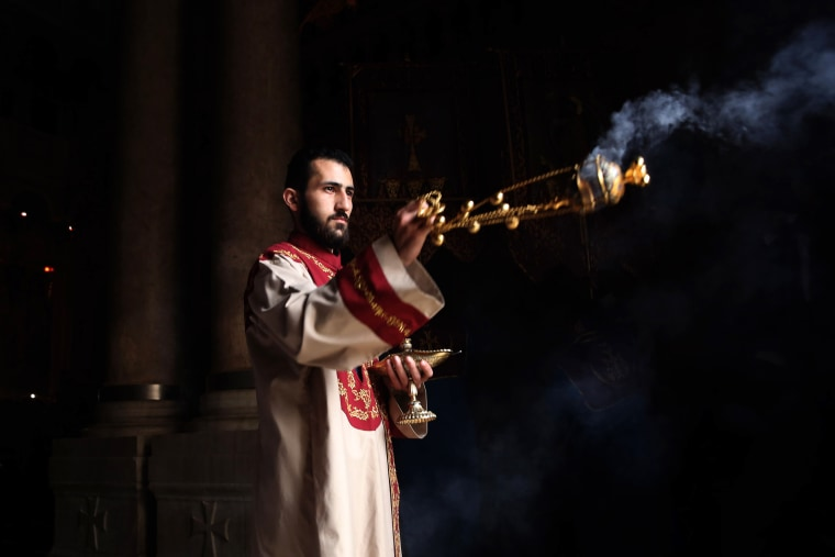 Image: A priest waves a censer during the Palm Sunday procession at the Church of the Holy Sepulchre, believed to be the traditional site of Jesus's resurrection, in Jerusalem on April 21.