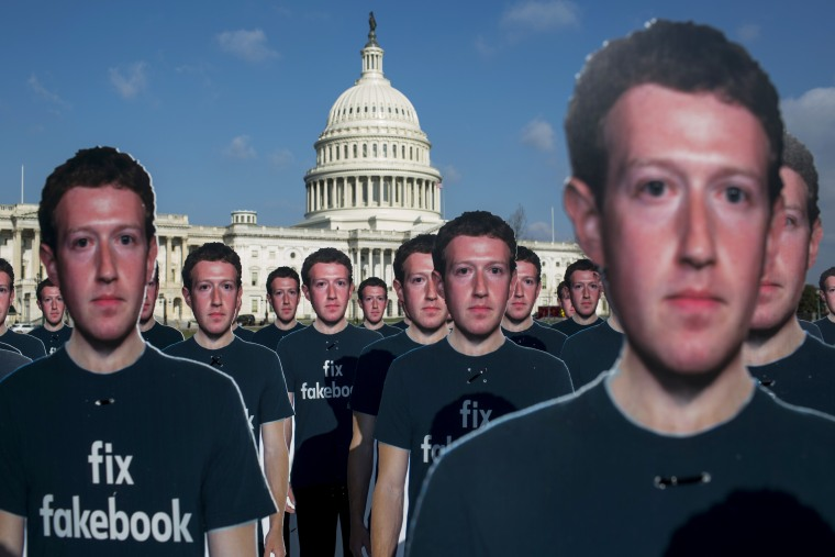 Image: Life-sized cutouts of Facebook CEO Mark Zuckerberg sit on the lawn of the Capitol before he appears at committee hearings on April 10, 2018.