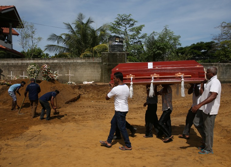 Image: A coffin is carried during the mass burial of victims at a cemetery near St. Sebastian Church in Negombo