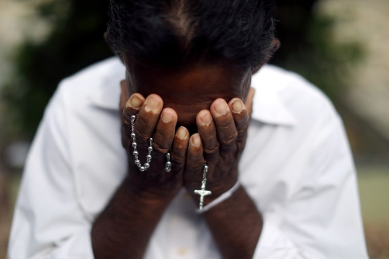 Image: A person mourns at a grave of a victim, two days after a string of suicide bomb attacks on churches and luxury hotels across the island on Easter Sunday, at Sellakanda Catholic cemetery in Negombo
