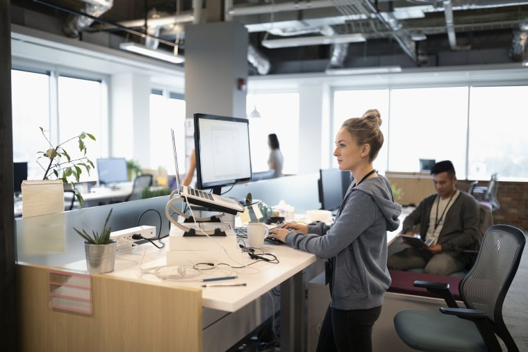 Image: Creative businesswoman standing at desk, using laptop and computer in open plan office