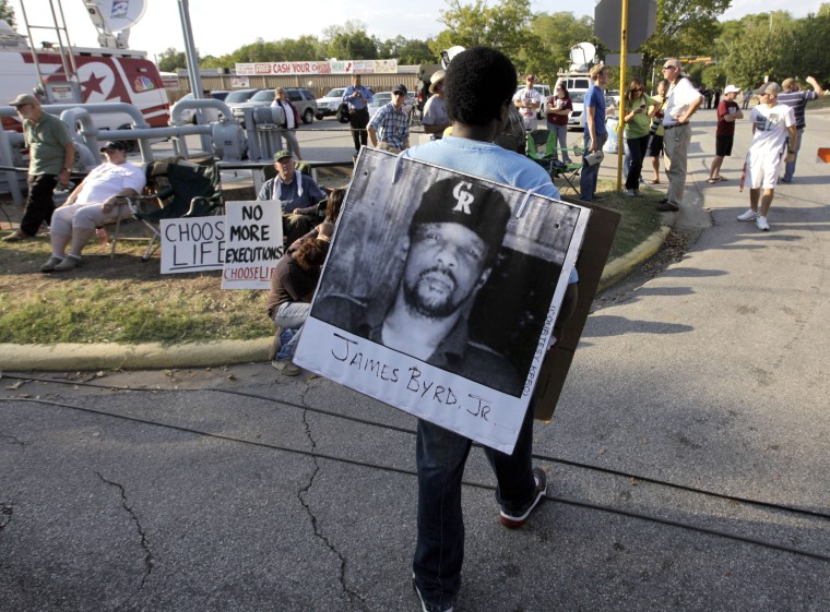 Image: Ricky Jason wears a photograph of James Byrd Jr. outside the Texas Department of Criminal Justice Huntsville Unit on Sept. 21, 2011.