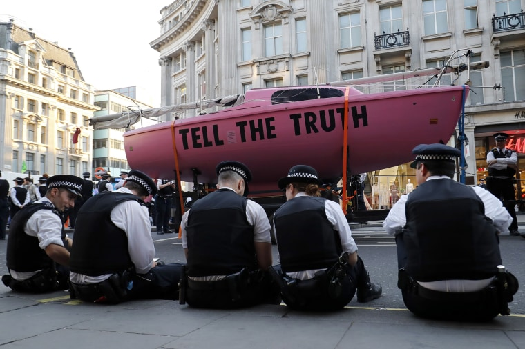 Image: Police officers surround the pink boat which climate change activists used as a central point of their encampment as they occupied the road junction at Oxford Circus in central London