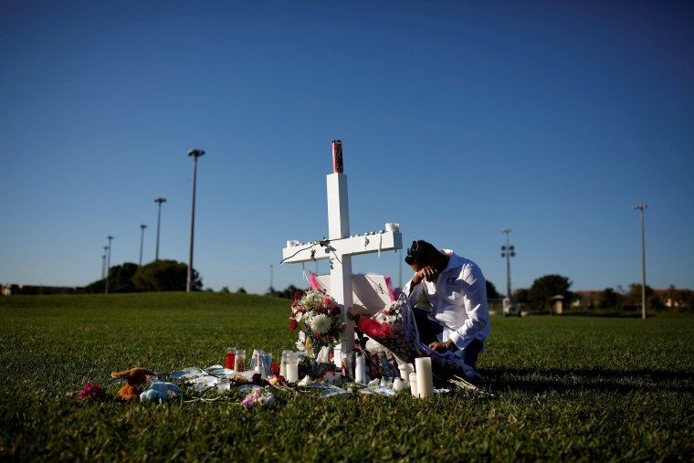 Image: Joe Zevuloni mourns in front of a cross placed in a park to commemorate the victims of the shooting at Marjory Stoneman Douglas High School, in Parkland