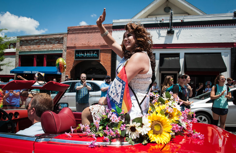 A participant waves from a car during Pride in Fayetteville, Arkansas, in 2018