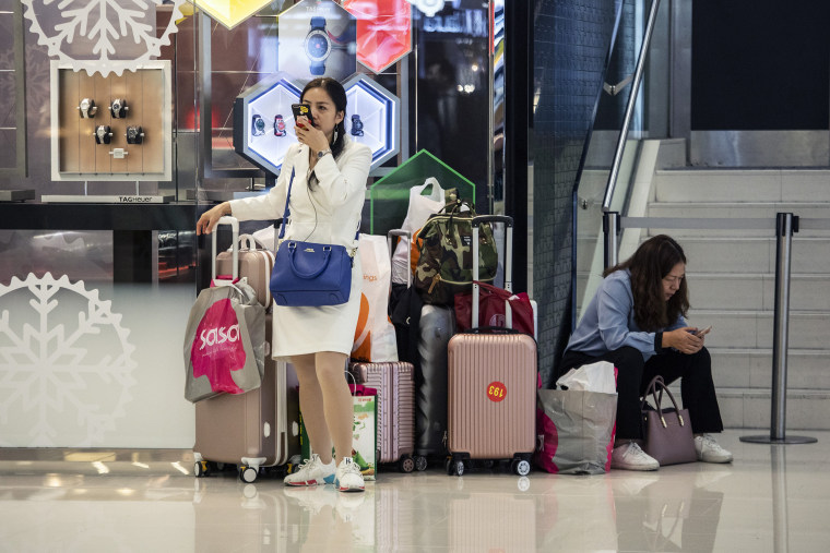 Image: Shoppers stand with suitcases and shopping bags inside Harbour City shopping mall in Hong Kong, China