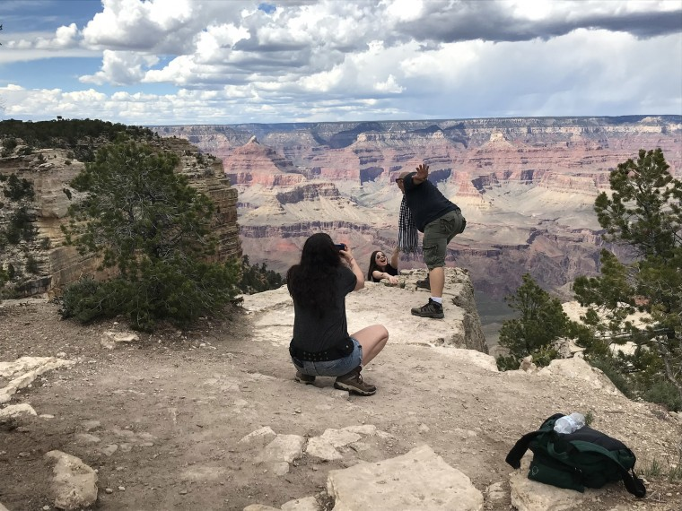 Image: Pat Shearer, 56, of Strawberry, Arizona, reaches for Victoria Gizhyrova, 29, of Chicago while Paloma Diaz, 48, of New York takes a photo staged to appear as if Shearer was saving Gizhyrova from falling from the edge of the South Rim in the Grand Ca