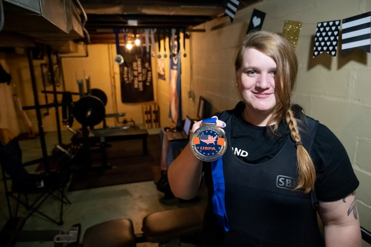 Photograph of JayCee Cooper holding a lifting medal.