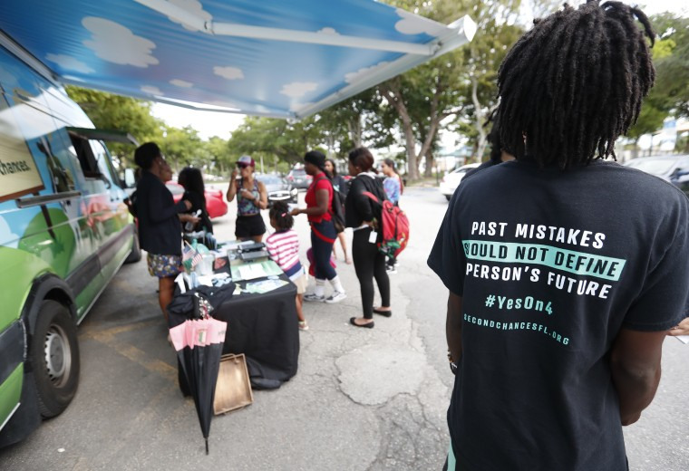 "People gather around a ""Yes on 4"" truck as they learn about Amendment 4, at Charles Hadley Park in Miami, on Oct. 22, 2018.  Amendment 4, was approved by Florida voters in November and could benefit an estimated 1.5 million former felons -- with the exception of murderers and felony sex offenders -- who had completed their sentences, including parole or probation."