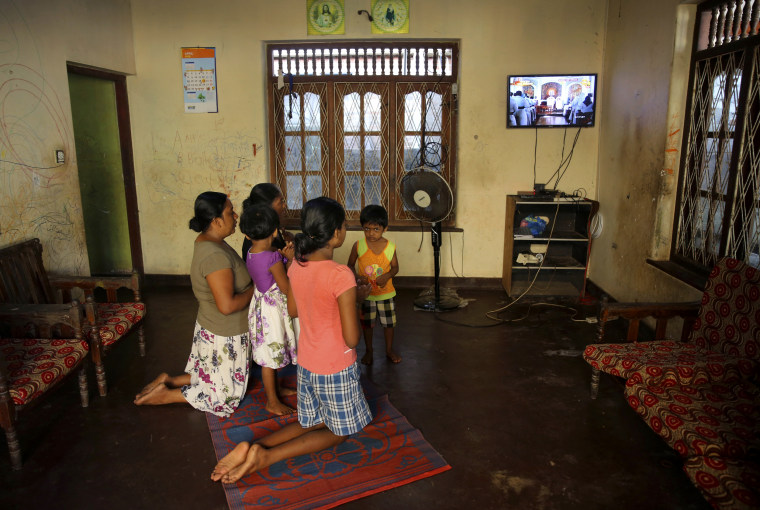 Image: A family prays inside their home while watching a live mass led by Sri Lankan Archbishop Cardinal Malcolm Ranjith in Negombo on April 28, 2019.