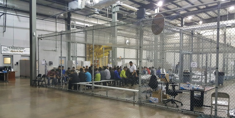 Image: People who've been taken into custody sit in one of the cages at a facility in McAllen, Texas