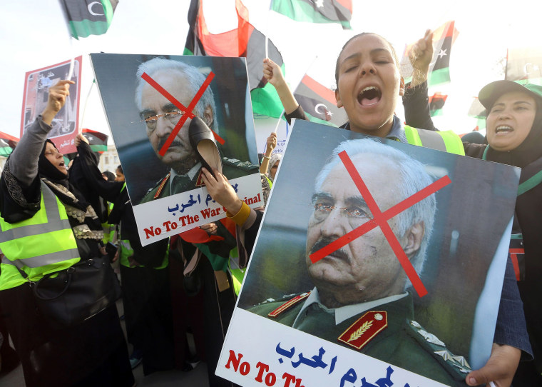 Image: A Libyan woman hits a portrait of Khalifa Haftar with a shoe