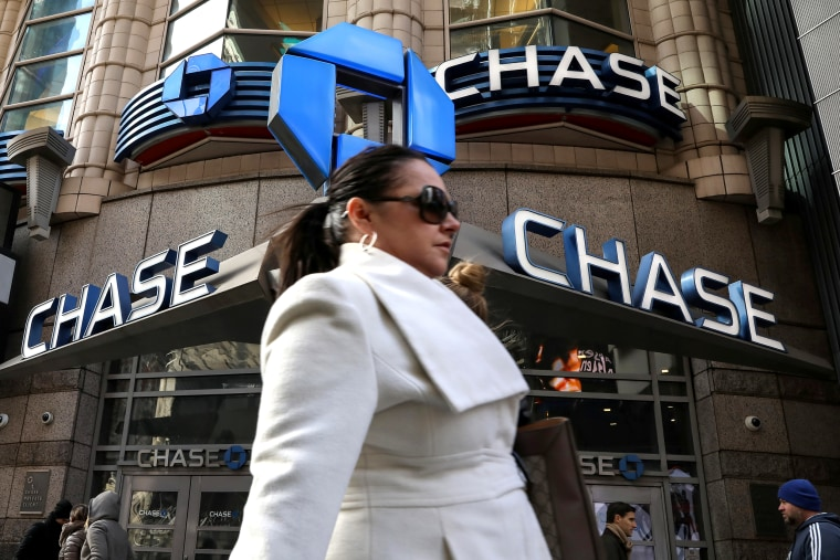 A woman passes by a Chase bank in Times Square in New York