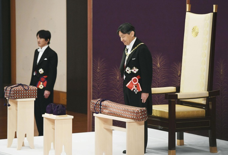 Image: Japan's Emperor Naruhito, flanked by Crown Prince Akishino, attends a ritual called Kenji-to-Shokei-no-gi, a ceremony for inheriting the imperial regalia and seals, at the Imperial Palace in Tokyo