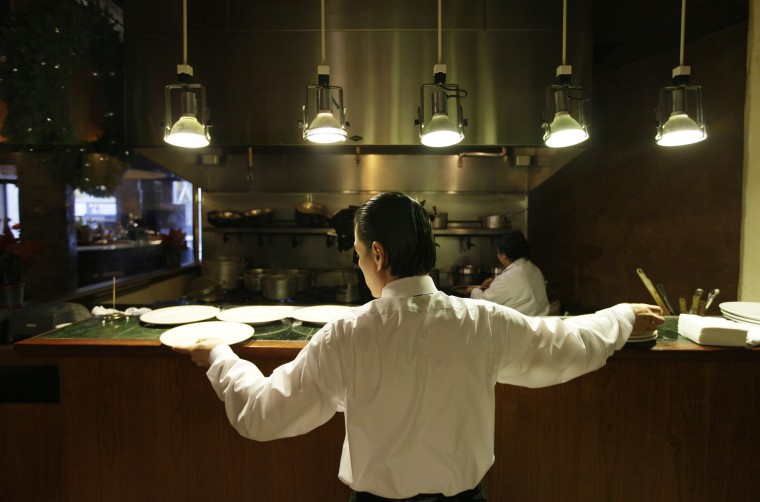 A waiter reaches for plates at a restaurant in San Francisco.
