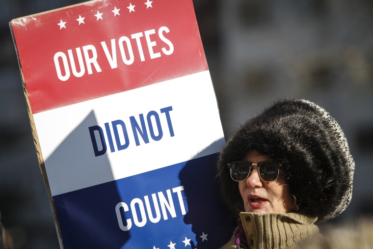 A protester at a rally at the Michigan State Capitol before the state electoral college met to cast their votes