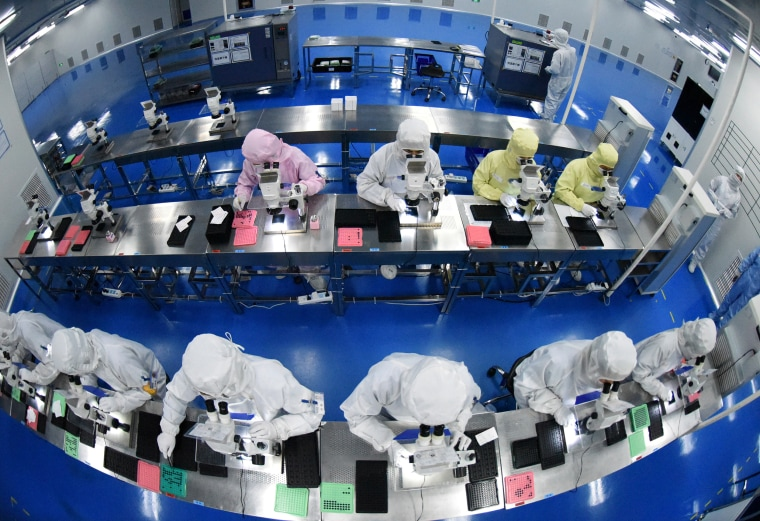 Employees work on a production line manufacturing camera lenses for cellphones at a factory in Lianyungang, Jiangsu