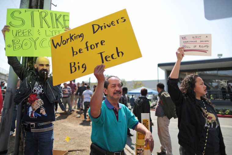 Striking Uber and Lyft drivers protest Uber's decision to cut per-mile pay from 80 cents to 60 cents, outside the Uber Hub in Redondo Beach