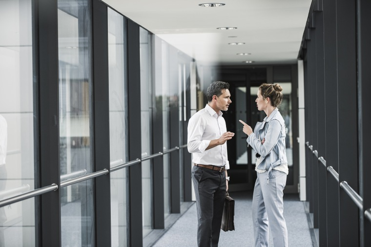 Image: Businesswoman and businessman discussing in office passageway