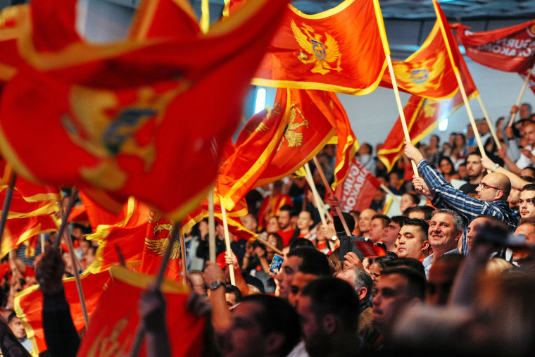Image: Supporters of Montenegrin Prime Minister Milo Djukanovic wave flags during an election rally in Podgorica