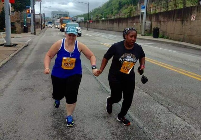 Image: Runners hold hands at the 25 mile marker during the Pittsburgh Marathon.