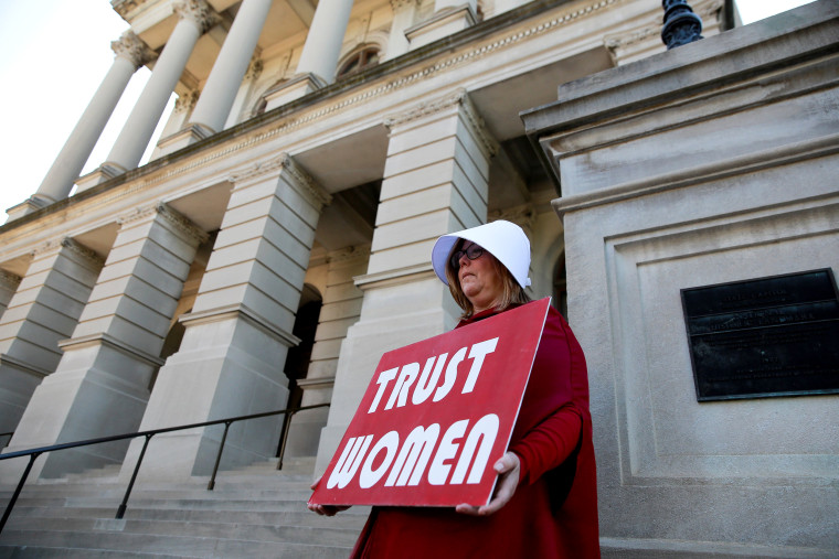 """Image: Michelle Disher, dressed as a Handmaid, protests Georgia's anti-abortion \""""heartbeat\"""" bill at the State Capitol in Atlanta on May 7, 2019."""