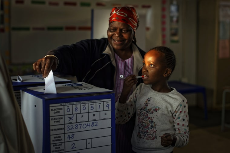 Image: A young girl accompanies a relative as she casts her vote the South African presidential election in Johannesburg on May 8, 2019.