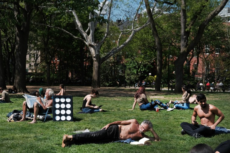 Image: Sunbathers relax in Washington Square Park in New York on May 8, 2019.