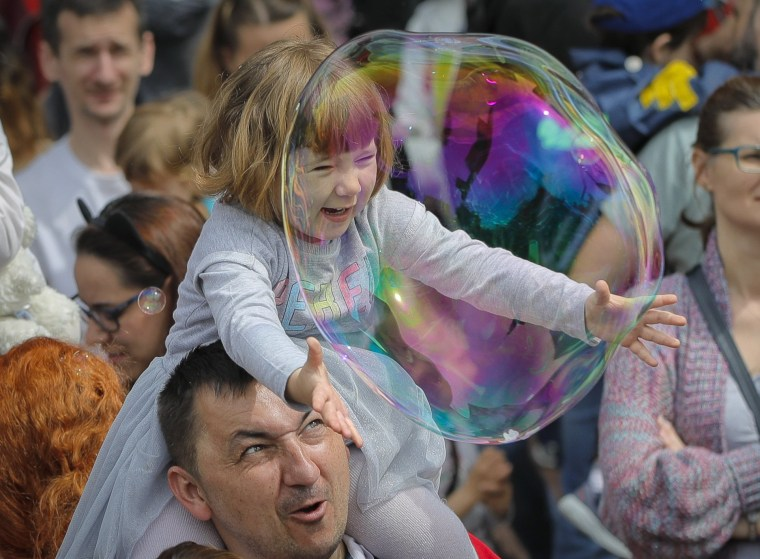 Image: A child reaches for a bubble at the Global Bubble Parade in Bucharest, Romania, on May 5, 2019. Soap bubble fans enjoy the international event held in 125 cities across 60 countries.