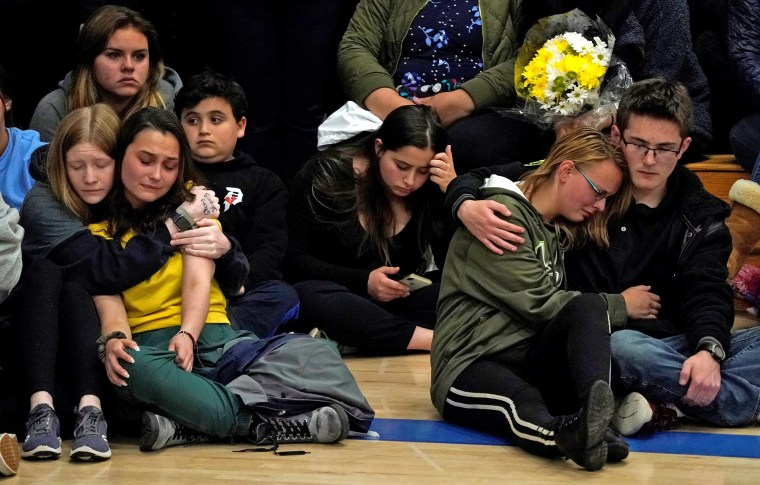 Image: Students hug at a vigil for the victims of the shooting at the Science, Technology, Engineering and Math (STEM) School in Highlands Ranch