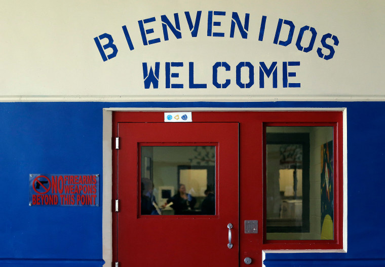 Image: A Spanish and English welcome sign is seen above a door in a secured entrance area at the Karnes County Residential Center in Karnes City, Texas