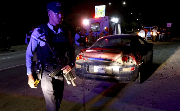 Image: Police investigate the scene after a man was found dead in a car after being stabbed in San Pedro Sula, Honduras, on May 1, 2019.