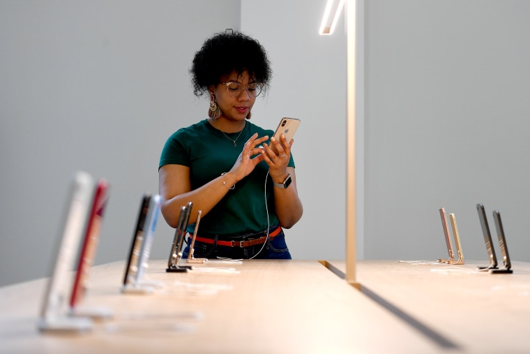 Image: An Apple Store employee uses an iPhone during the grand opening and media preview of the new Apple Carnegie Library store in Washington