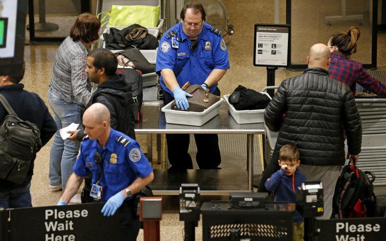 Image:  A TSA agent helps passengers at Salt Lake City International Airport on Jan 16. 2019.