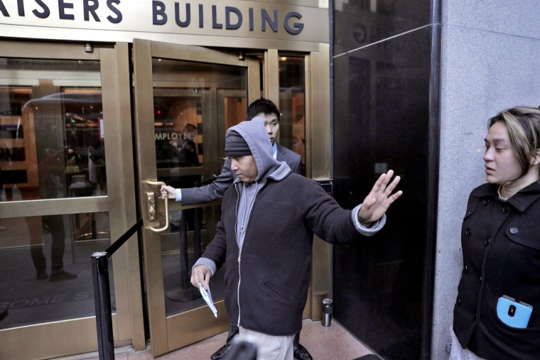 Hay Hov waves to supporters as he and his wife, Catherine Depooter-Hov, enter the U.S. Immigration and Customs Enforcement offices in San Francisco where he turned himself over to ICE officials, on March 13, 2019.