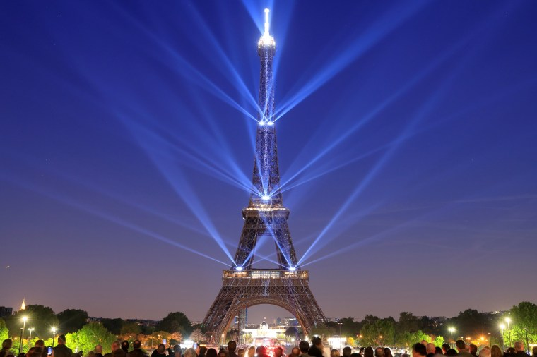 Image: The Eiffel tower is illuminated during a light show to celebrate its 130th anniversary in Paris