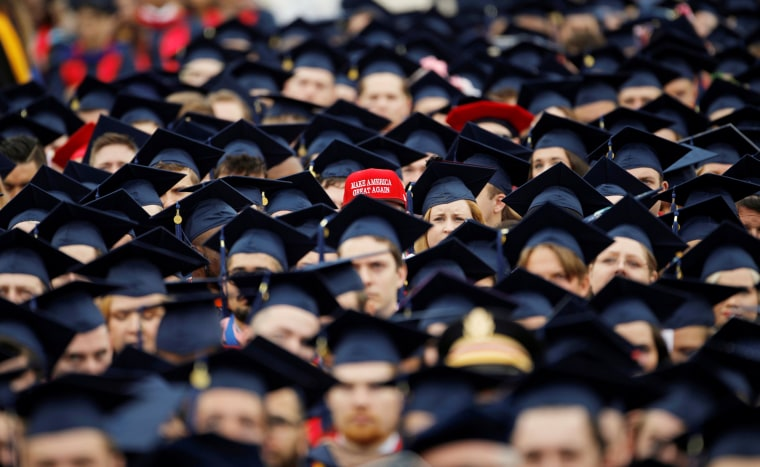Image: A graduate wears a MAGA hat before the start of commencement exercises at Liberty University in Lynchburg, Virginia