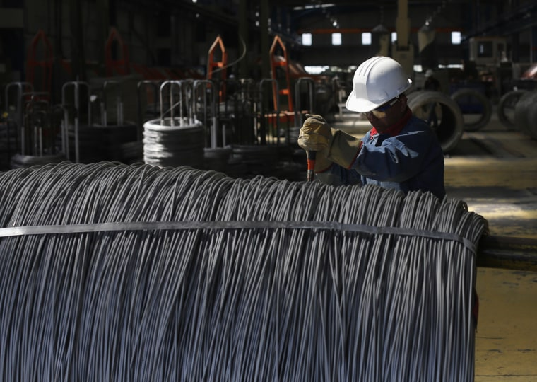 Worker inspects wire rod at TIM stainless steel wire factory in Huamantla
