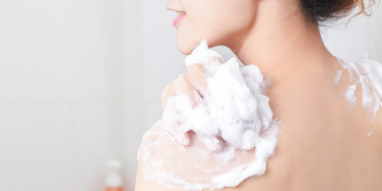 Midsection Of Woman Applying Soap On Back
