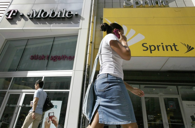 Image: A woman talking on her phone as she walks past T-mobile and Sprint wireless stores in New York