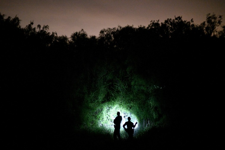 Image: Border patrol agents search from undocumented migrants crossing the Rio Grande near Palmview, Texas, on April 6, 2019.