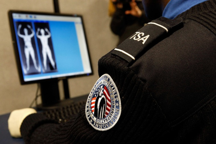 "Image: Transportation Security Administration Security Officer Nyamsi Tchapleu looks at images created by a ""backscatter"" scanner at Ronald Reagan National Airport"