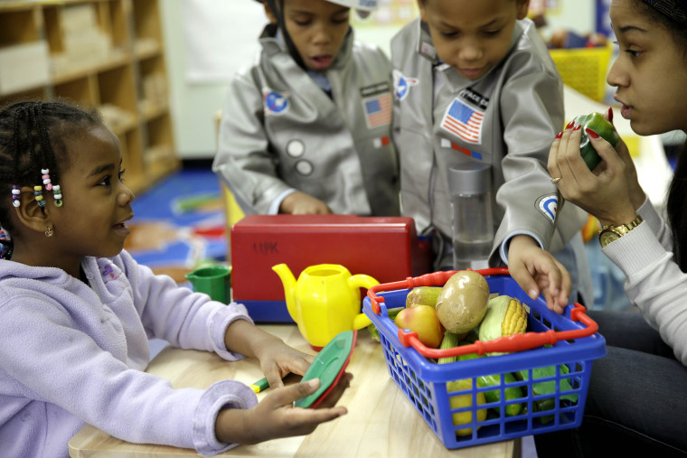 Oumou Balde, 4, left, plays with her teacher Jacqualine Sanchez, right, and pretend food in a pre-kindergarten class at the Sheltering Arms Learning Center in New York in a program to educate children about nutrition and health on, Jan. 21, 2014.
