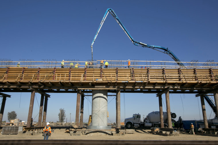 Workers pour concrete on one of the elevated sections of the high-speed rail that will cross over the San Joaquin River, near Fresno, California, in 2018.